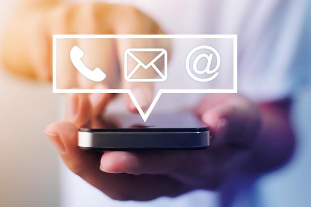 Zakończenie Wizerunek Samiec Wręcza Używać Smartphone Z Ikona Telefonu Emaila Telefonem Komórkowym I Adresem. Skontaktuj Się Z Nami Koncepcja Marketingu I E-mail Marketingu Premium Zdjęcia