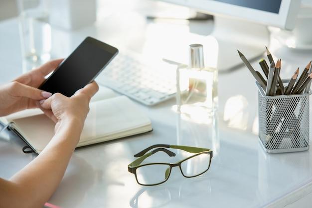 Zakończenie żeńskie Ręki Używać Telefon Podczas Gdy Pracujący Na Komputerze Przy Nowożytnym Biurowym Wnętrzem Darmowe Zdjęcia