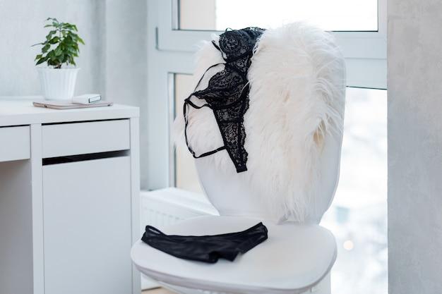 Zakupy I Moda, Koncepcja Kobiecej Garderoby. Zestaw Efektownej Stylowej Seksownej Bielizny Koronkowej Na Białym Krześle, Wnętrze Loftu. Akcesoria Dla Kobiet Premium Zdjęcia