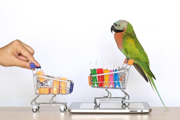Zakupy Online, Parrot Na Miniaturowym Modelu Koszyka I Torbie Na Smartfonie Z Tabletem Premium Zdjęcia