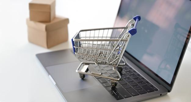 Zakupy online pojęcie: wózek na zakupy na laptopie Premium Zdjęcia