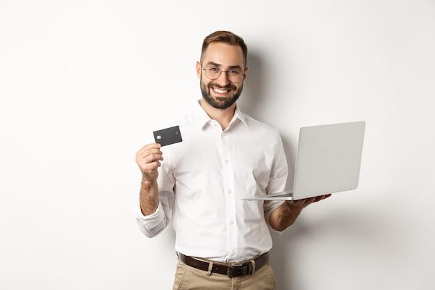 Zakupy Online. Przystojny Mężczyzna Pokazano Kartę Kredytową I Za Pomocą Laptopa Na Zamówienie W Internecie, Stojąc Darmowe Zdjęcia