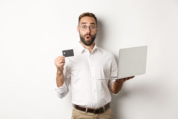 Zakupy Online. Zaskoczony Mężczyzna Posiadający Laptop I Kartę Kredytową, Sklep Internetowy, Stojący Darmowe Zdjęcia