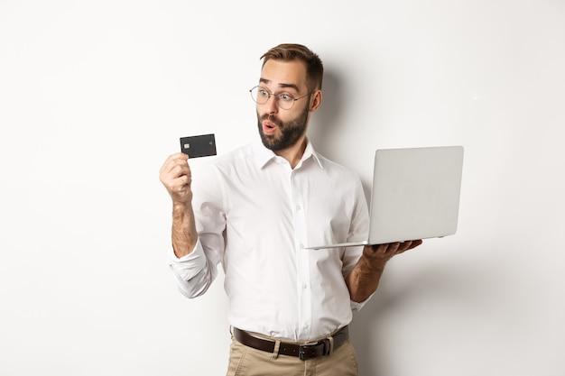 Zakupy Online. Zdumiony Biznesmen Posiadania Laptopa, Patrząc Pod Wrażeniem Karty Kredytowej, Stojąc Darmowe Zdjęcia