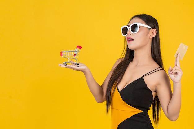 Zakupy piękna kobieta trzyma furę w jej ręce na kolorze żółtym. Darmowe Zdjęcia