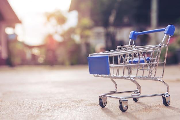 Zakupy Pojęcie: Mała Błękit Pusta Wózek Na Zakupy Zabawka Na Betonowej Podłoga. Rynek Zakupów Premium Zdjęcia