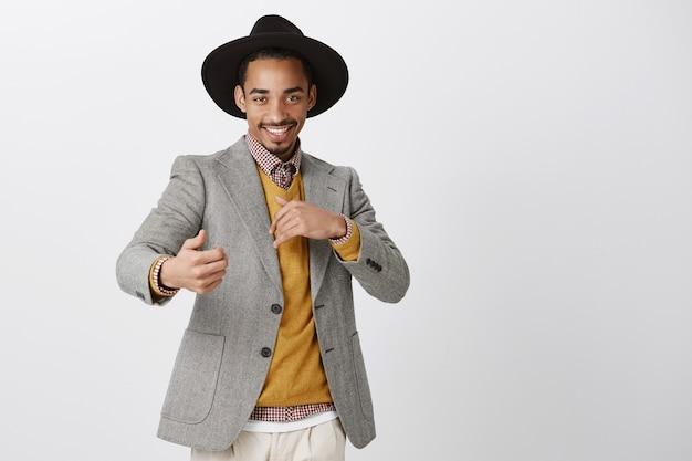 Zalotny, Romantyczny Mężczyzna, Który Chce Się Bawić. Zadowolony Pewny Siebie Afroamerykanin W Stylowym Czarnym Kapeluszu I Kurtce, Wykonujący Zmysłowe I Namiętne Gesty, Uśmiechający Się Ciekawie Nad Szarą ścianą Darmowe Zdjęcia