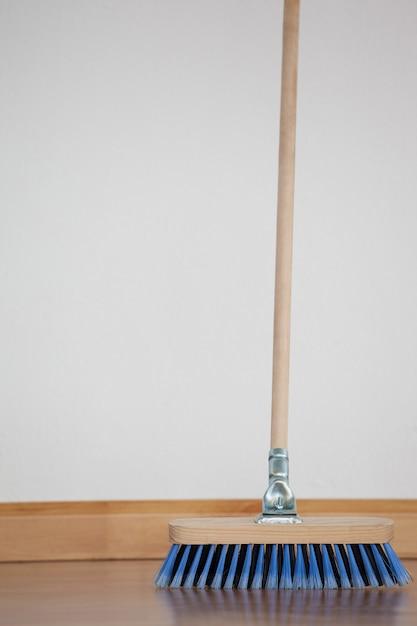 Zamiatająca miotła z drewnianym uchwytem na podłodze Premium Zdjęcia