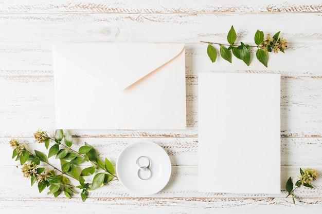 Zamknięta koperta; karta; gałązka kwiatów i obrączki na talerzu nad białym biurkiem Darmowe Zdjęcia