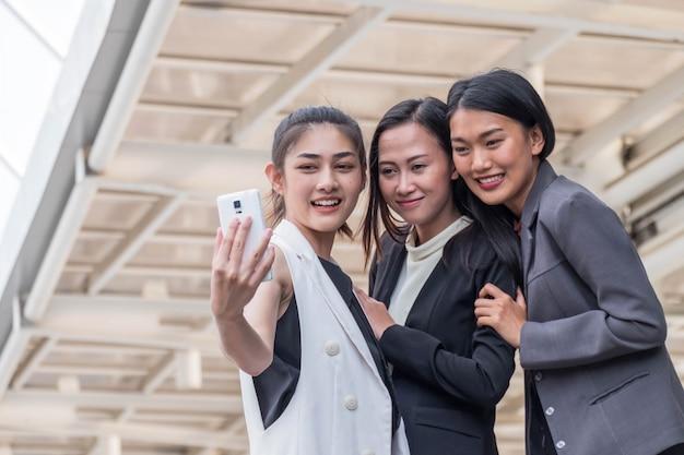 Zamknięty młoda kobieta biznesu drużyna outdoors ustawia brać selfie Premium Zdjęcia