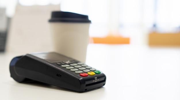 Zamknij Automat Do Kart Kredytowych Przy Stole Z Białą Filiżanką Kawy Na Stole W Kawiarni, Płatności Zbliżeniowe Premium Zdjęcia