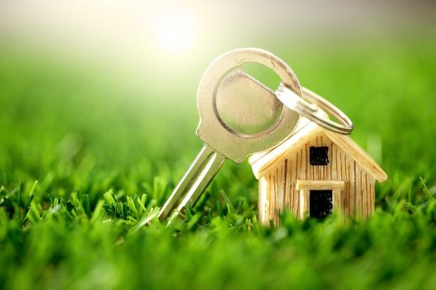 Zamknij model domu, miejsce na zielonej trawie na hipotekę i pożyczki mieszkaniowe, refinansowanie lub inwestycję w nieruchomości Premium Zdjęcia
