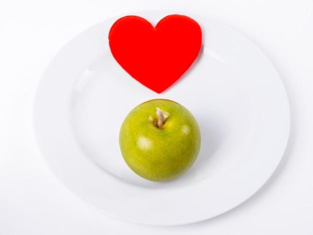 Zamknij Się Czerwone Serce Z Zielonym Jabłkiem Na Białym Talerzu Premium Zdjęcia