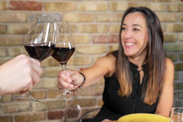 Zamknij Się Młoda Para Opiekania Kieliszkami Czerwonego Wina W Restauracji Premium Zdjęcia