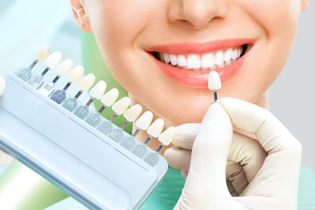 Zamknij Się Portret Młodych Kobiet W Fotelu U Dentysty, Sprawdź I Wybierz Kolor Zębów. Dentysta Wykonuje Proces Leczenia W Gabinecie Stomatologicznym. Wybielanie Zębów Premium Zdjęcia