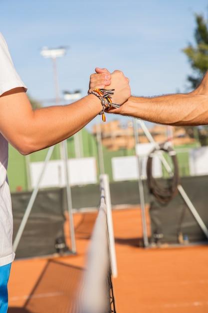 Zamknij się z dwóch profesjonalnych tenisistów trzymając ręce nad siatką tenisową przed meczem. Premium Zdjęcia