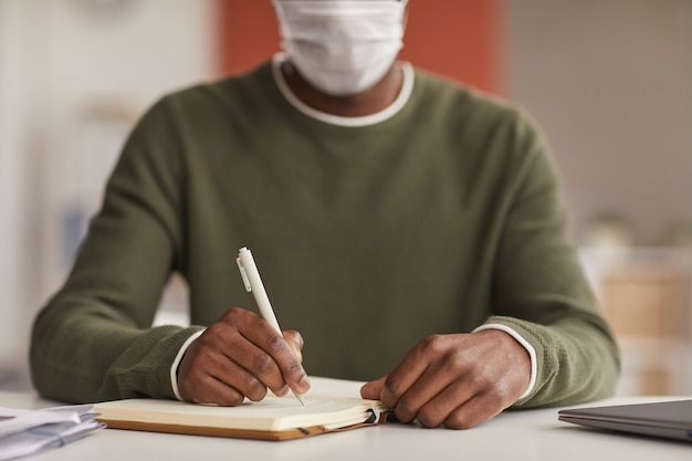Zamknij Się Z Nie Do Poznania African American Człowieka Noszącego Maskę Podczas Pisania W Planowaniu Przy Biurku W Biurze, Kopia Przestrzeń Premium Zdjęcia