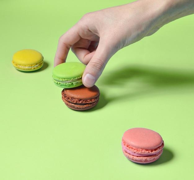 Zamknij Się Z Ręki Trzymającej Kolorowe Makaroniki Premium Zdjęcia