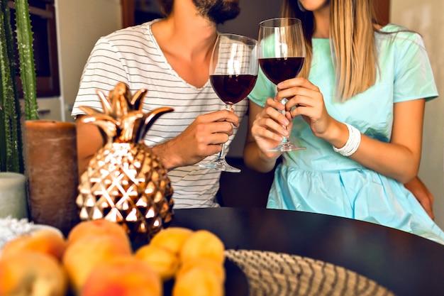 Zamknij Szczegóły Romantycznego Wieczoru ładnej Pary Pijącej Czerwone Wino, Ciesząc Się Razem, Nowoczesne Wnętrze I Modne Eleganckie Ubrania. Darmowe Zdjęcia