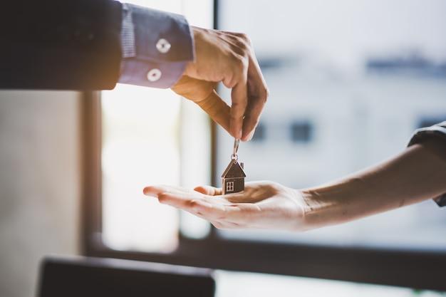 Zamknij widok strony nieruchomości / właściciela dając klucz do domu kupującego / najemcy. Premium Zdjęcia