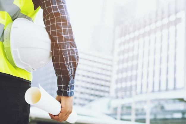 Zamknij Widok Z Przodu Inżyniera Męskiego Pracownika Budowlanego, Trzymając Biały Kask Ochronny I Nosić Odzież Odblaskową Dla Bezpieczeństwa Operacji Pracy. Premium Zdjęcia