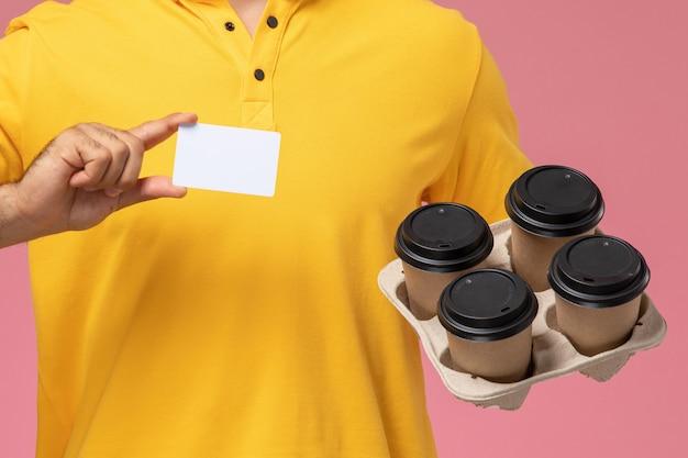 Zamknij Widok Z Przodu Kurier Męski W żółtym Mundurze Trzymający Plastikową Kartę I Dostawy Filiżanek Kawy Na Różowym Tle Darmowe Zdjęcia
