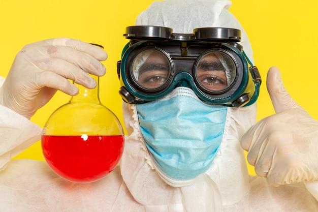 Zamknij Widok Z Przodu Mężczyzna Naukowiec W Specjalnym Kombinezonie Ochronnym I Masce Trzymającej Kolbę Z Czerwonym Roztworem Na żółtym Biurku Darmowe Zdjęcia