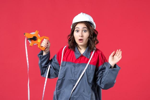 Zamknij Widok Zaskoczony Architekta Kobiet W Mundurze Na Sobie Kask Z Miarką Na Czerwonej ścianie Darmowe Zdjęcia