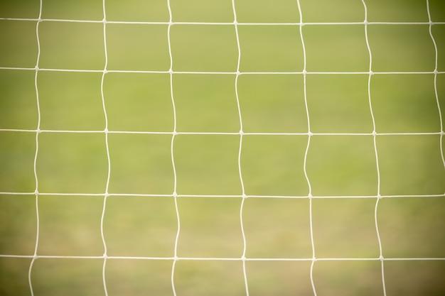 Zamyka Up Biała Futbolu, Piłki Nożnej Celu Sieć Z Zieloną Trawą Jako Tło Używać Jako Sport Tapeta Lub Tło. Premium Zdjęcia