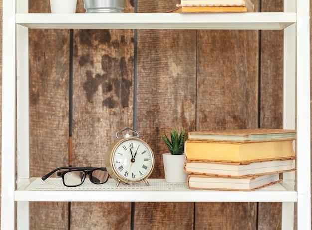 Zamyka up biały półka na książki przeciw grunge drewnianej ścianie Premium Zdjęcia