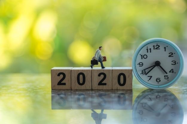 Zamyka Up Biznesmen Miniatury Postać Z Torebka Bieg Na Drewnianym 2020 Numerowym Bloku Z Round Zegarem I Zieleń Liścia Naturą. Premium Zdjęcia