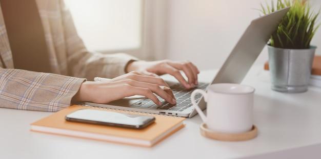 Zamyka up bizneswoman pisać na maszynie na laptopie Premium Zdjęcia