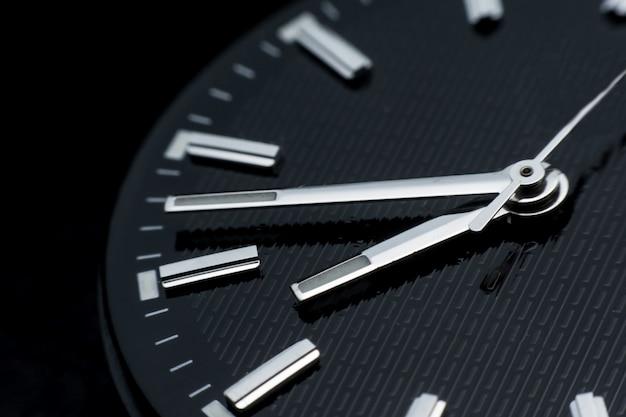 Zamyka up clockwise na czarnym zegarowej twarzy tle. zegarek na rękę w stylu retro Premium Zdjęcia