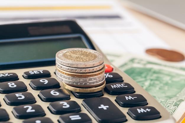 Zamyka Up Kalkulator I Monety Na Biznesowym Tle Premium Zdjęcia
