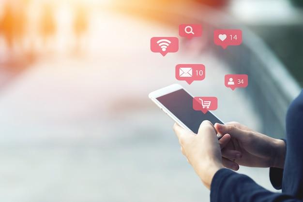 Zamyka up kobieta używa jego mobilnego smartphone plenerowego. zakupy online koncepcji. Premium Zdjęcia