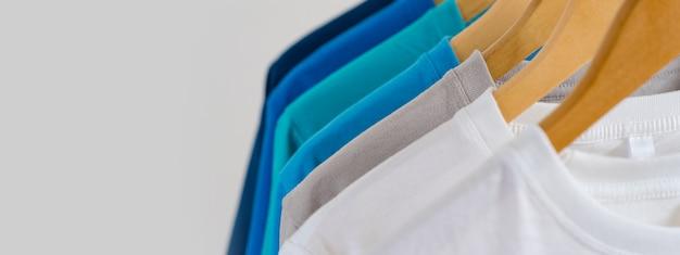 Zamyka up kolorowe koszulki na wieszakach, odzieży tło Premium Zdjęcia