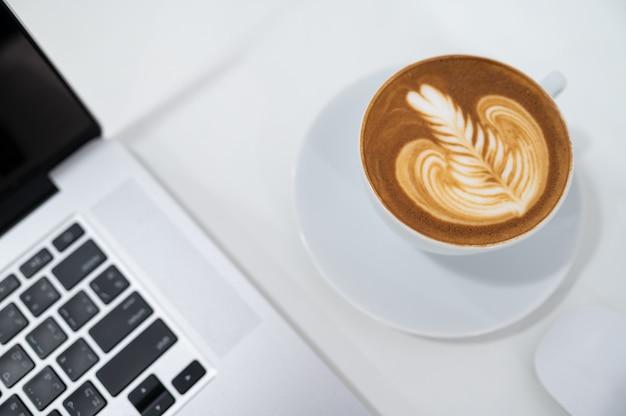 Zamyka Up Latte Sztuki Filiżanka Z Klawiaturą Laptop Premium Zdjęcia