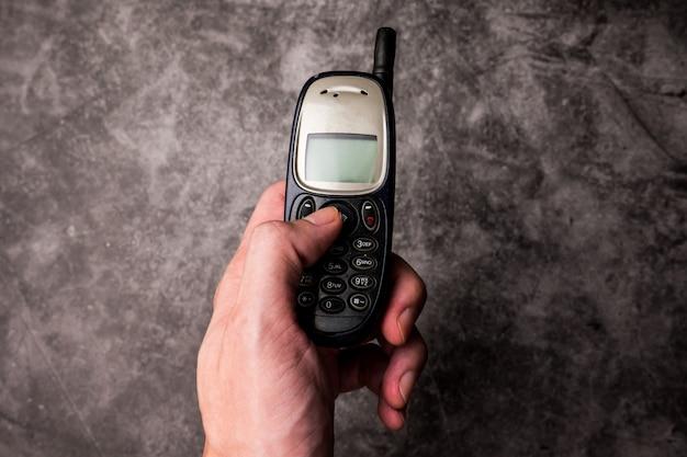 Zamyka Up Męska Ręki Prasa Na Guziku Przestarzały Telefon Komórkowy. Premium Zdjęcia