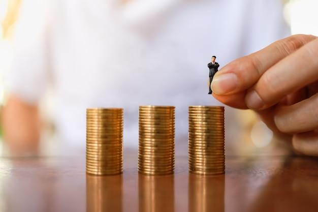 Zamyka Up Mężczyzna Ręki Mienia Biznesmena Miniatury Postaci Ludzie I Kładzenie Wierzchołek Stos Złociste Monety. Premium Zdjęcia