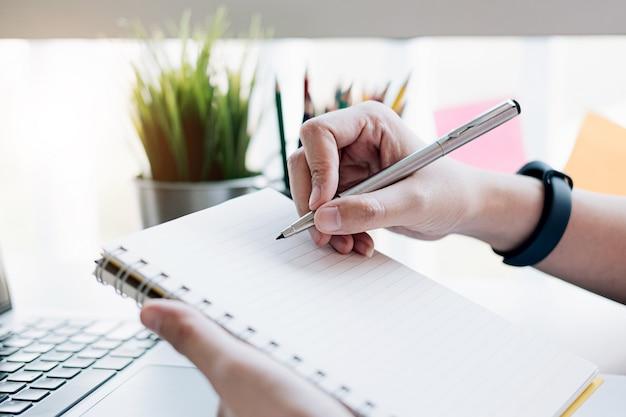 Zamyka up mężczyzna writing w notatniku. Premium Zdjęcia