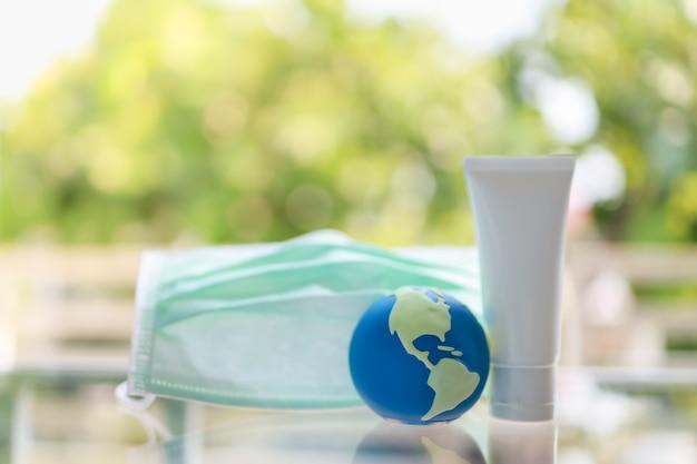 Zamyka Up Mini światowa Piłka Z Chirurgicznie Twarzy Maską I Butelka Alkoholu Gel Sanitizer Z Zielonym Natury Tłem. Premium Zdjęcia