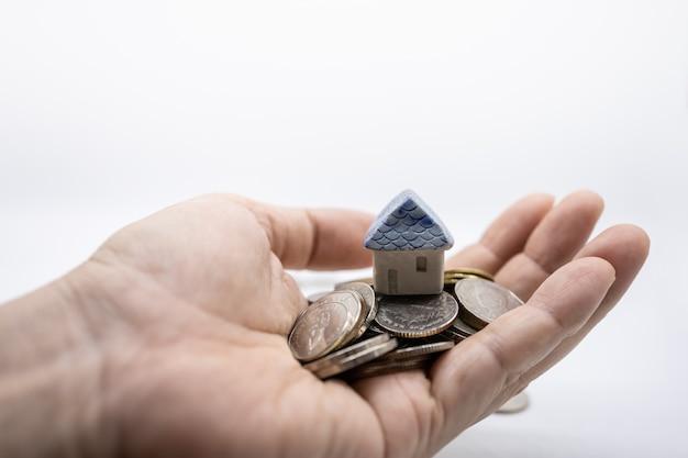 Zamyka up mini zabawka dom na górze stosu monet na mężczyzna ręce z bielem. Premium Zdjęcia