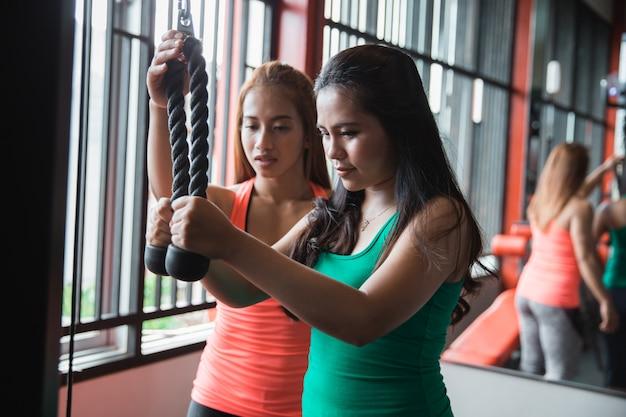 Zamyka Up Młoda Kobieta ćwiczy Triceps Pushdown Z Trenerem Premium Zdjęcia