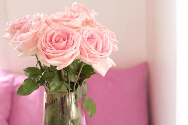 Zamyka up piękny bukiet różowe róże w szklanej wazie na stole przy żywym pokojem. Premium Zdjęcia