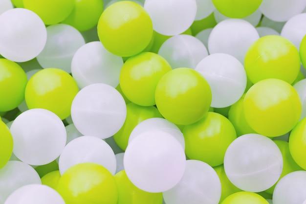 Zamyka Up Plastikowe Białe I żółte Piłki W Suchym Basenie Na Boisku Premium Zdjęcia