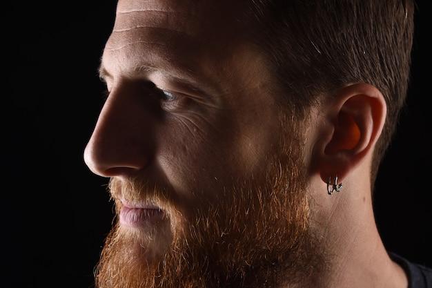 Zamyka up portret profil zadumany mężczyzna na czerni Premium Zdjęcia