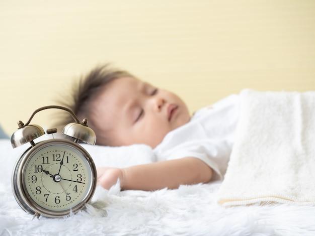 Zamyka up przy budzikiem i zamazuje chłopiec podczas gdy śpiący na łóżku. Premium Zdjęcia