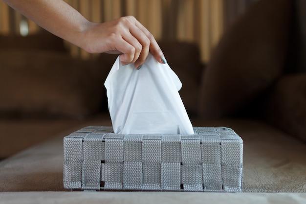 Zamyka Up Ręki Kobieta Podnosi Białego Bibułkę Od Szarego Pudełka. Premium Zdjęcia