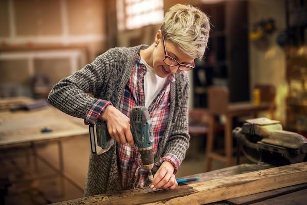 Zamyka Up Rozochocona Pracowita Krótkiego Włosy Kobieta Pracuje Z Elektrycznym świderem W Tkaninowym Warsztacie Premium Zdjęcia