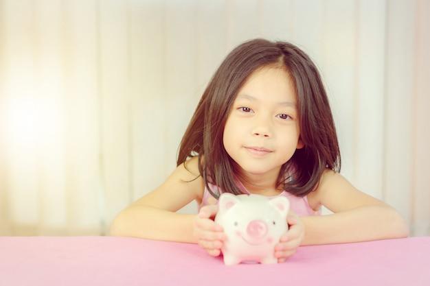 Zamyka up śliczna mała dziewczynka z prosiątko bankiem, dzieciaka oszczędzania pojęcie. Premium Zdjęcia
